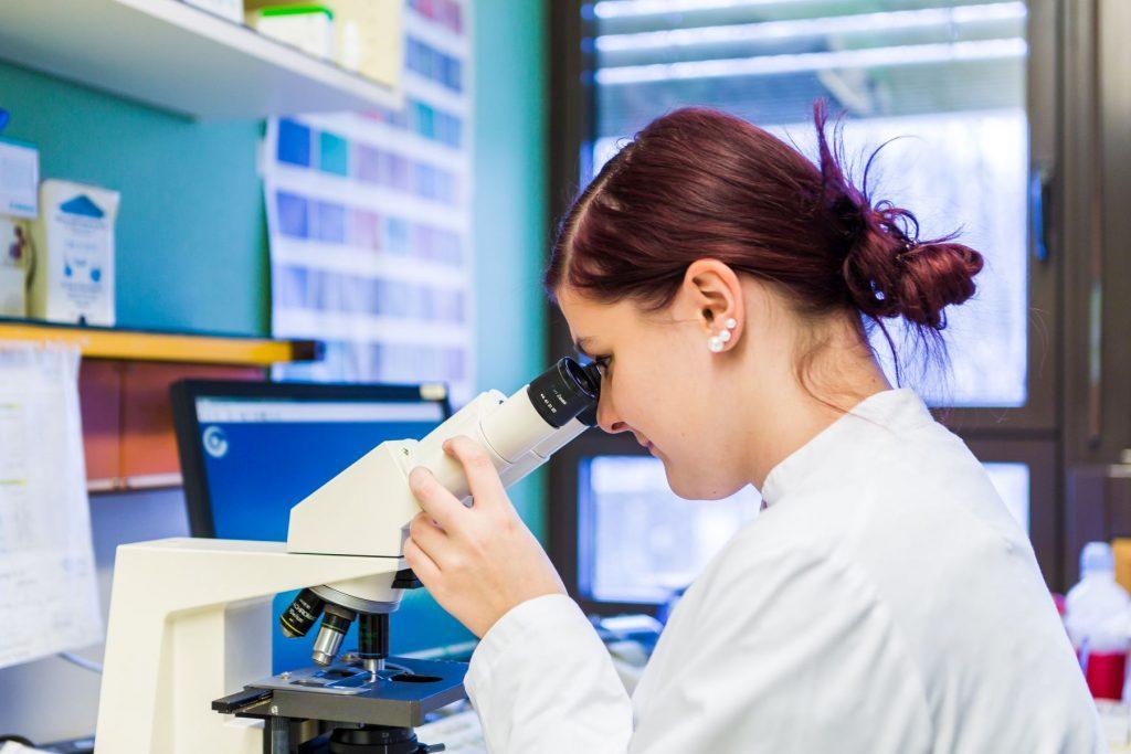 Eine Mitarbeiterin des Labors im Klinikum Ingolstadt blickt durch ein Mikroskop.