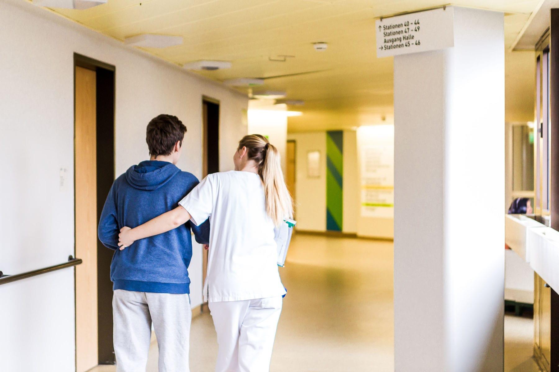 Eine Krankenschwester stützt einen Patienten beim Gehen