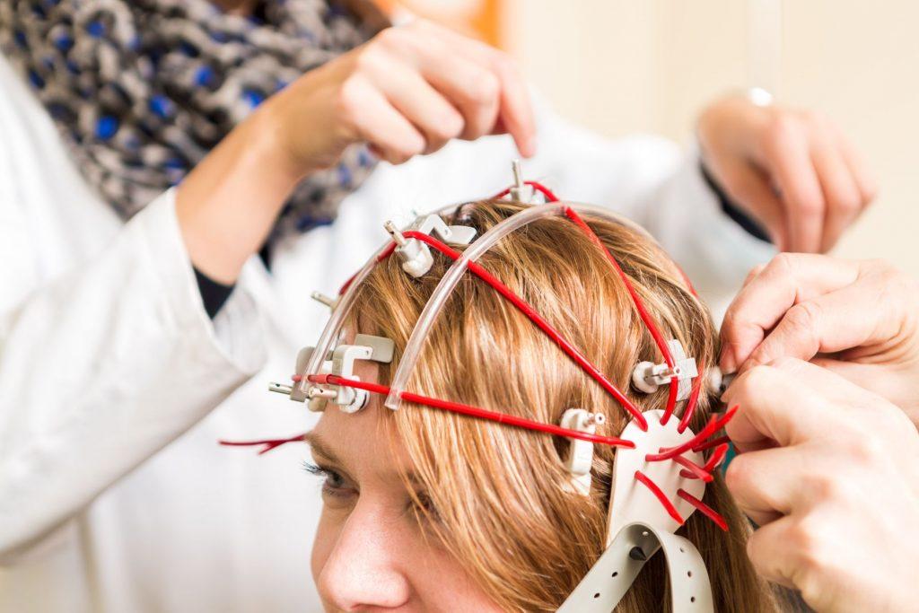 Bei einer Patientin wird ein EEG durchgeführt.
