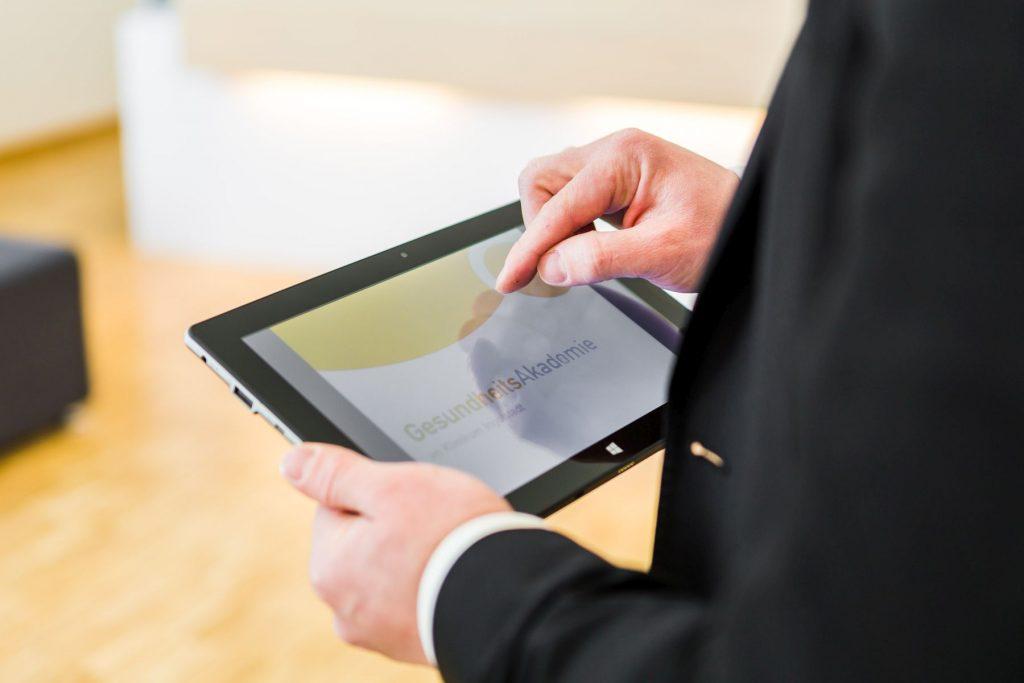 Ein Mann hält ein Tablet.
