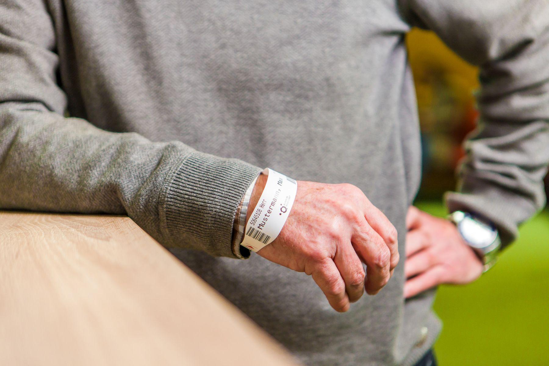 Ein älterer Herr trägt am rechten Handgelenk ein Patientenarmband des Klinikums Ingolstadt