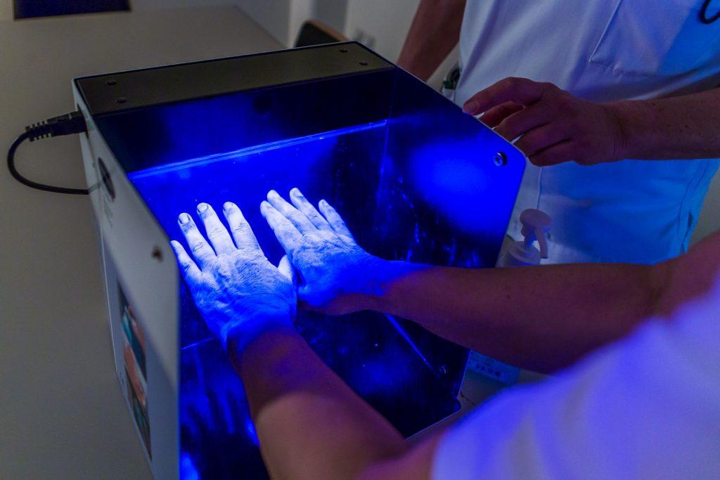 Unter einer UV-Lampe wird getestet, ob man sich die Hände richtig desinfiziert hat
