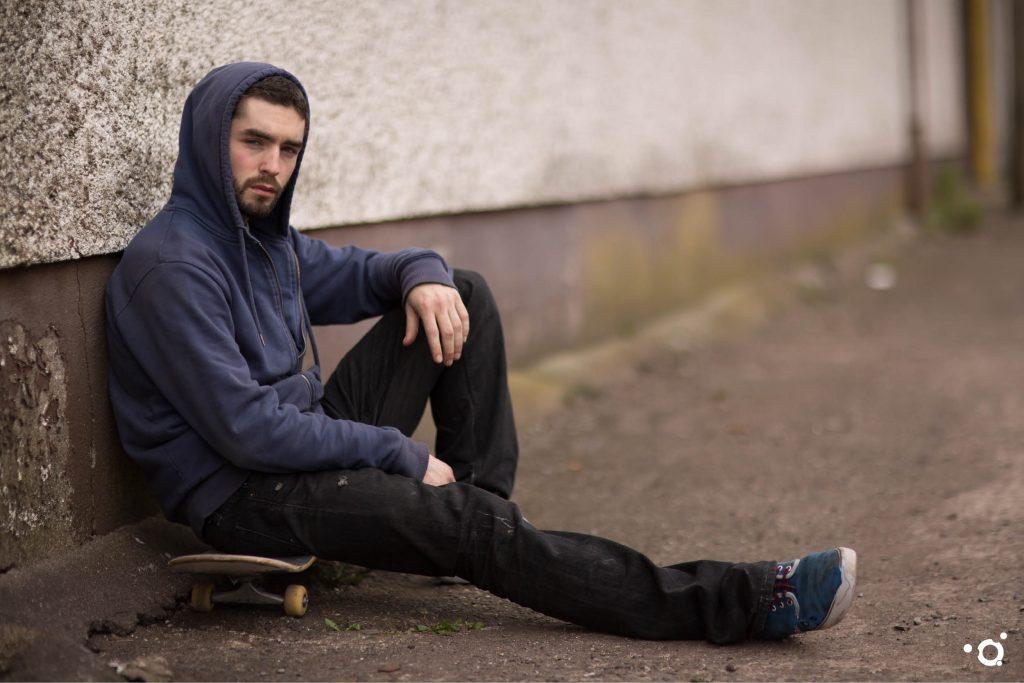 Junger Mann sitzt am Boden
