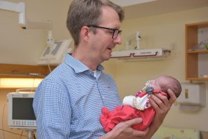 Dr. Micha Bahr mit einem Baby im Arm