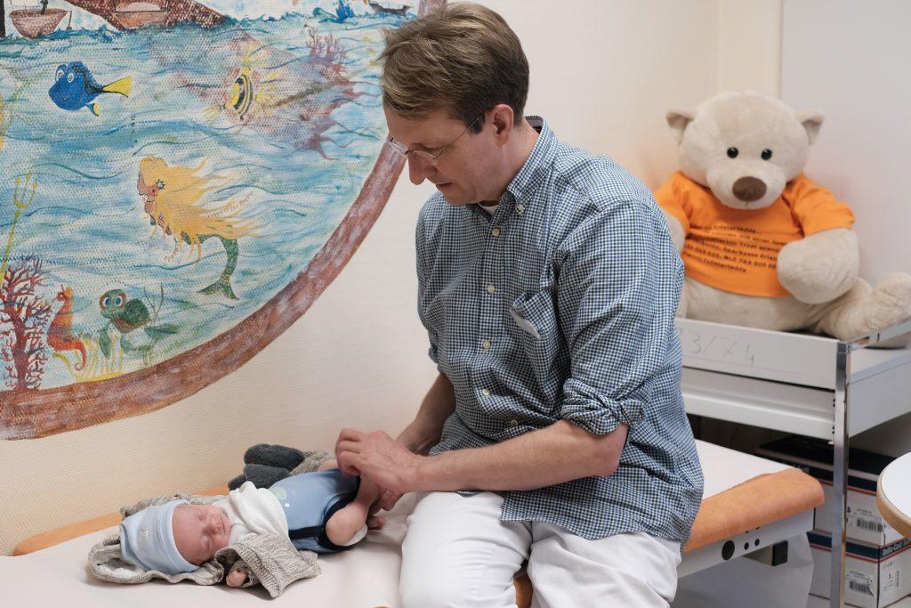 Dr. Micha Bahr untersucht ein kleines Baby