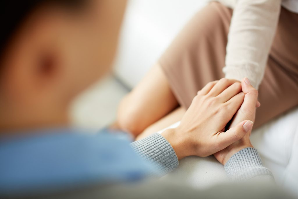 Eine Psychologin hält mitfühlend die Hand einer Patientin