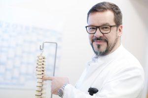 Dr. Robert Morrison zeigt auf ein Modell einer Wirbelsäule