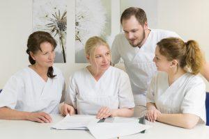 Vier Pflegekräfte besprechen im Sitzen eine Patientenakte.