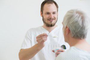 Ein Pfleger hilft einem älteren Herren bei der Nahrungsaufnahme.