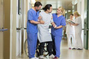 Zwei Pflegefachkräfte helfen einem Patienten aus seinem Rollstuhl