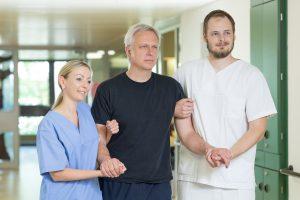 Zwei Pflegekräfte des Klinikums Ingolstadt stützen einen älteren Herren beim Gehen.