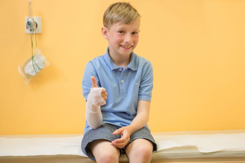 Ein Junge hält den Daumen nach oben, nachdem er einen Verband erhalten hat