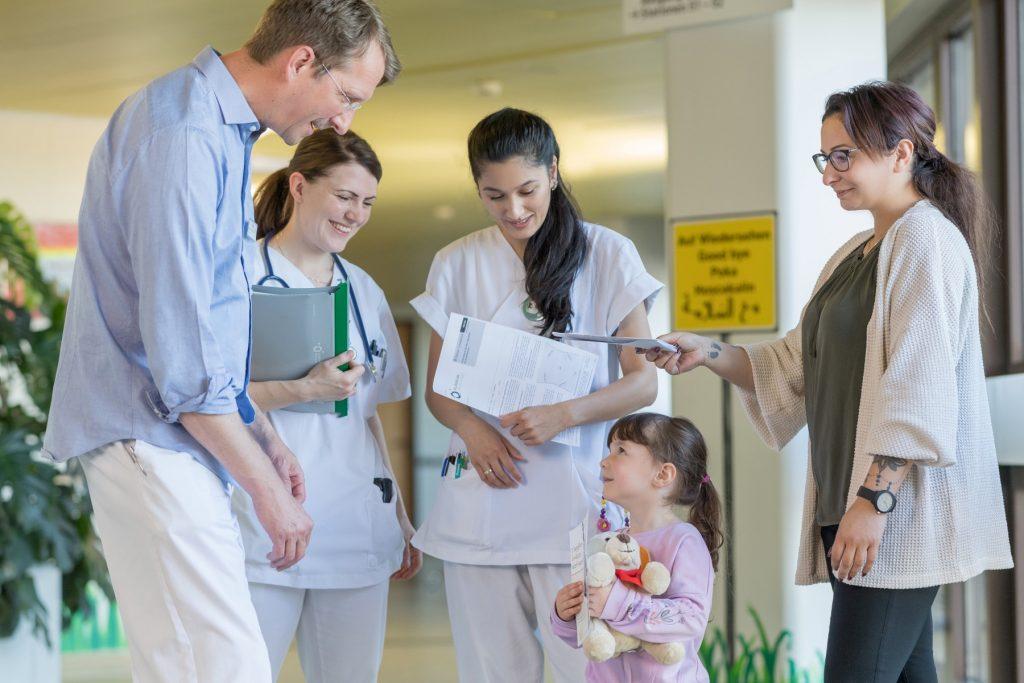 Dr. Bahr und die Stationsschwestern verabschieden ein Kind und seine Mutter