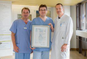 Oberarzt Dr. Rainer Dabitz, Stationsleiter Thomas Flierler und Klinikdirektor Prof. Dr. Thomas Pfefferkorn mit dem Zertifikat der Stroke Unit