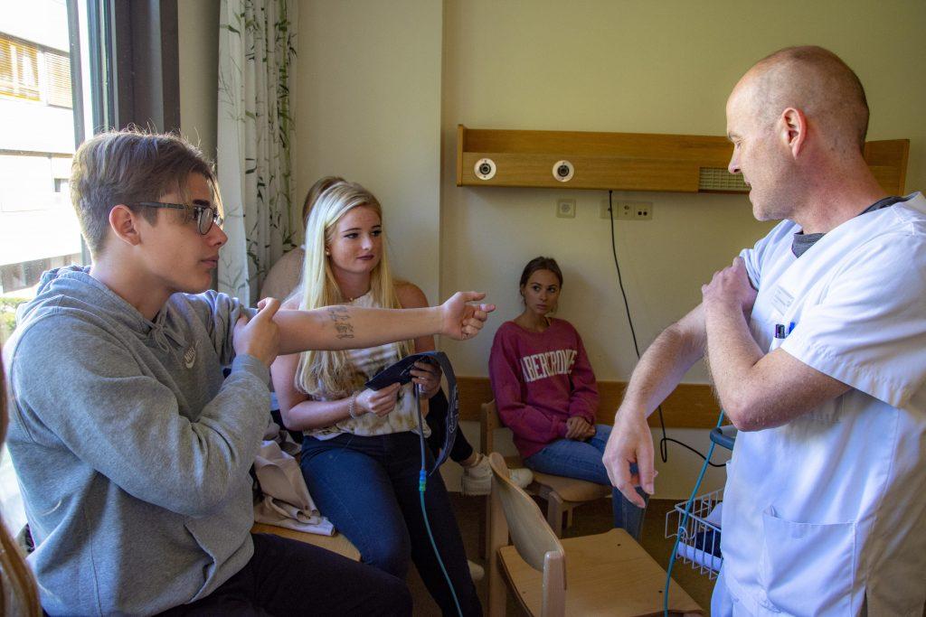 Der Praxisanleiter erklärt, wie die jungen Frauen und Männer ein Blutdruckgerät bedienen und die Manschette anlegen.