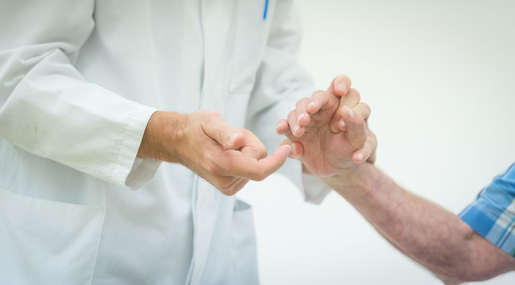 Neurologie - ein Arzt testet die Reflexe an den Fingern eines Patienten