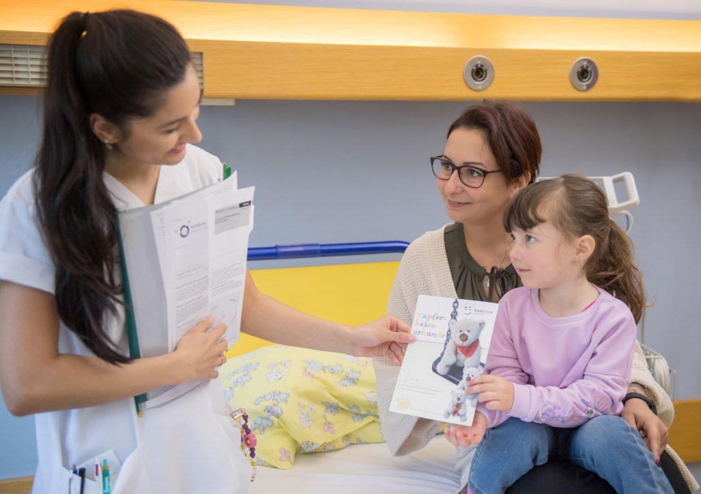 Pflegekraft mit kleinem Mädchen und deren Mutter