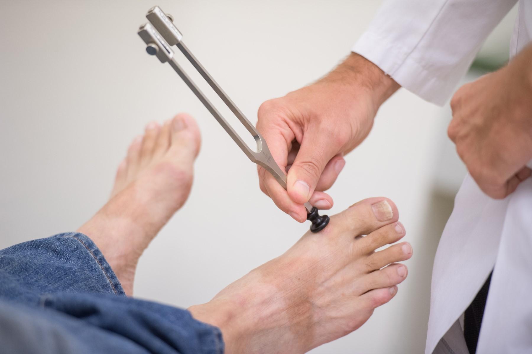 Stimmgabeltest am Fuß eines Patienten
