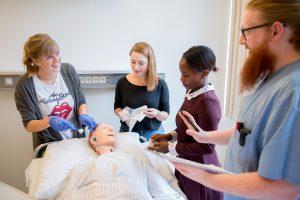 Ein Pfleger erklärt drei Schülerinnen wie sie einen Patienten richtig versorgen