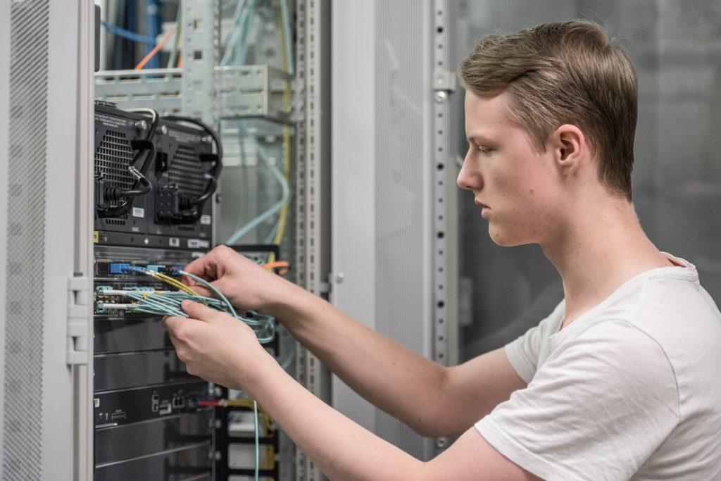 Ein Azubi arbeitet im Serverraum des Klinikums Ingolstadt
