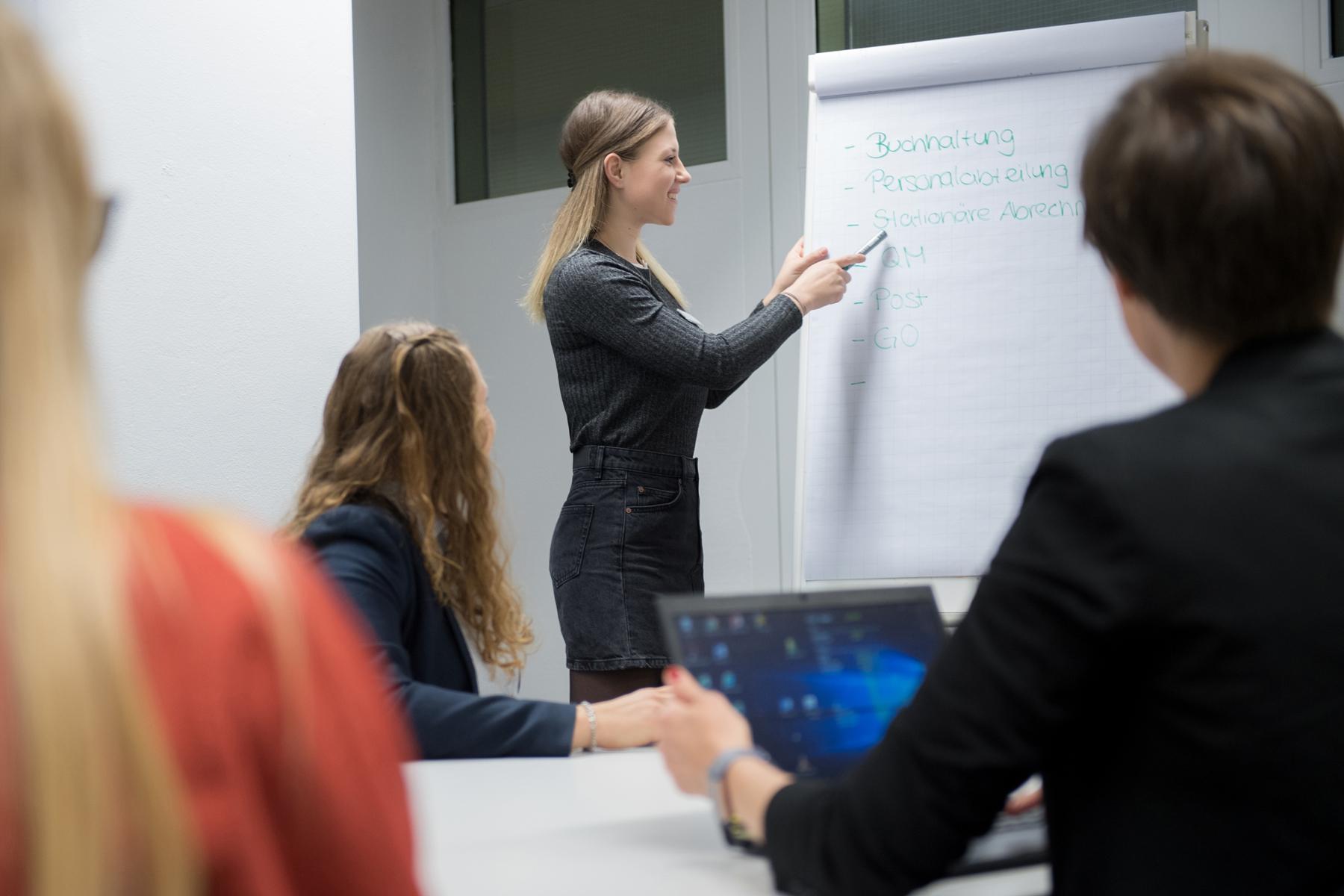 Eine Auszubildende erklärt verschiedene Fachbegriffe am Flipchart.