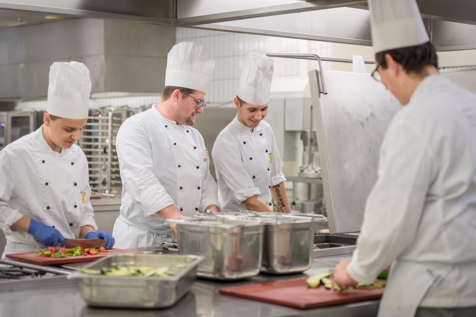 Ein Koch des Klinikums Ingolstadt erklärt einem Azubis, wie man Paprika richtig schneidet