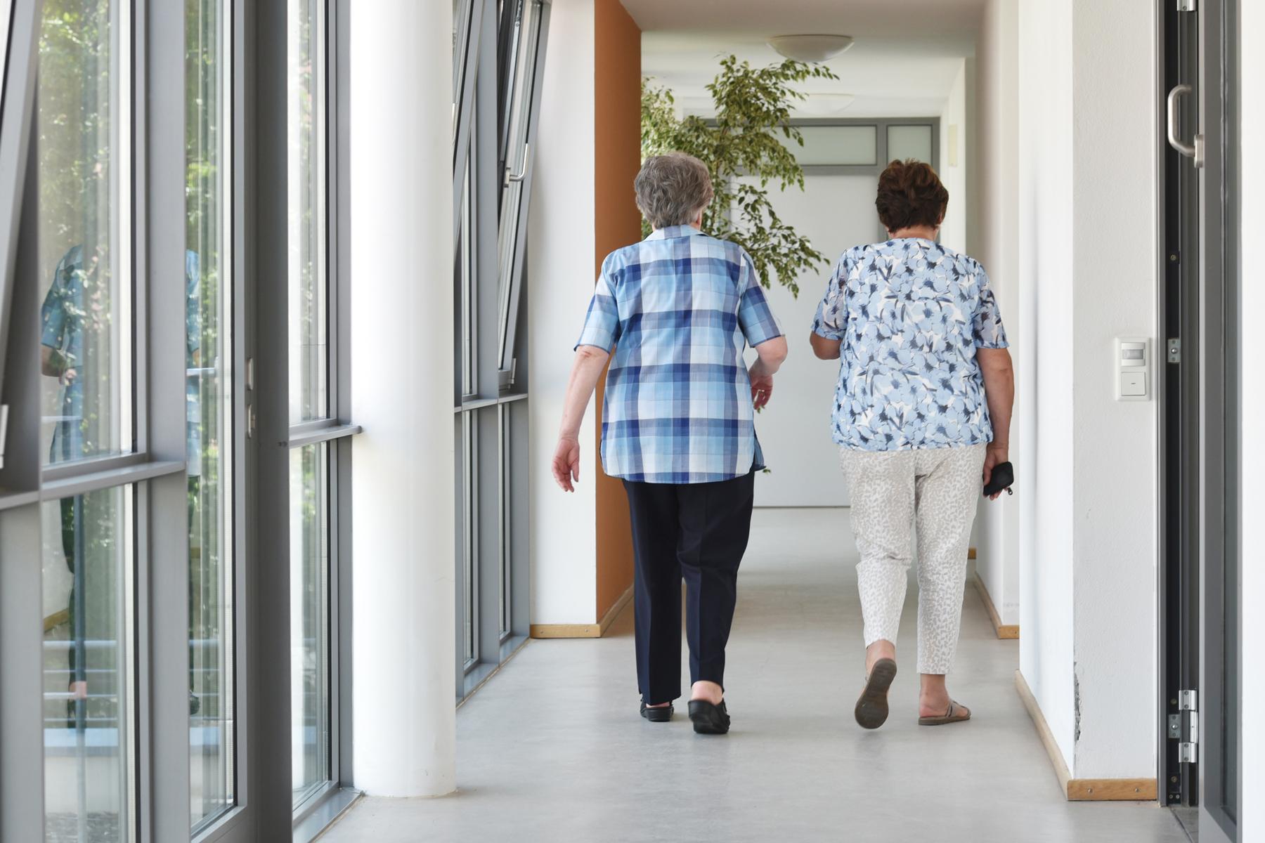 Zwei ältere Damen gehen einen Flur entlang