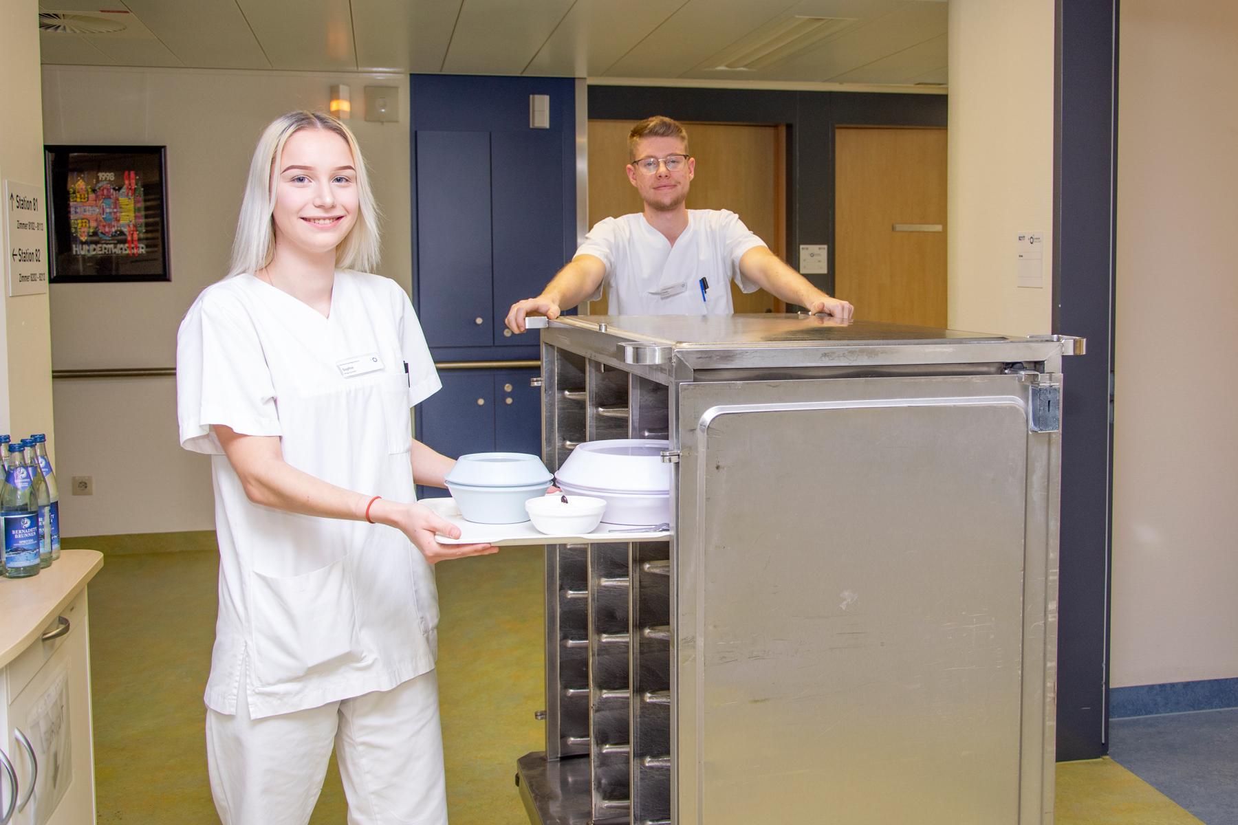 Zwei Bufdis im Klinikum Ingolstadt verteilen Essen auf Station.