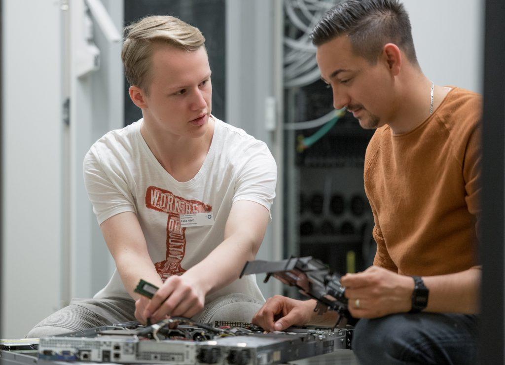 Ein Azubi zum Fachinformatiker im Klinikum Ingolstadt baut mit einem Kollegen einen Rechner zusammen.
