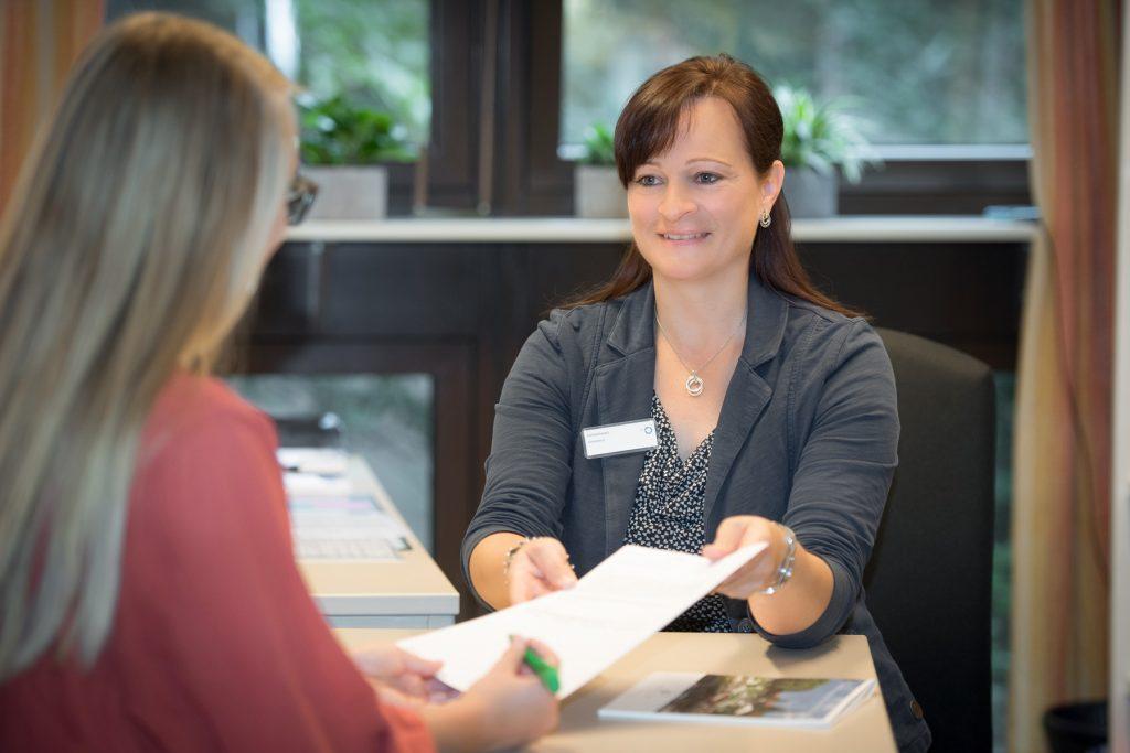 Eine Mitarbeiterin des Sozialdienstes im Klinikum Ingolstadt erklärt eine Patientin wie man das Dokument richtig ausfüllt.