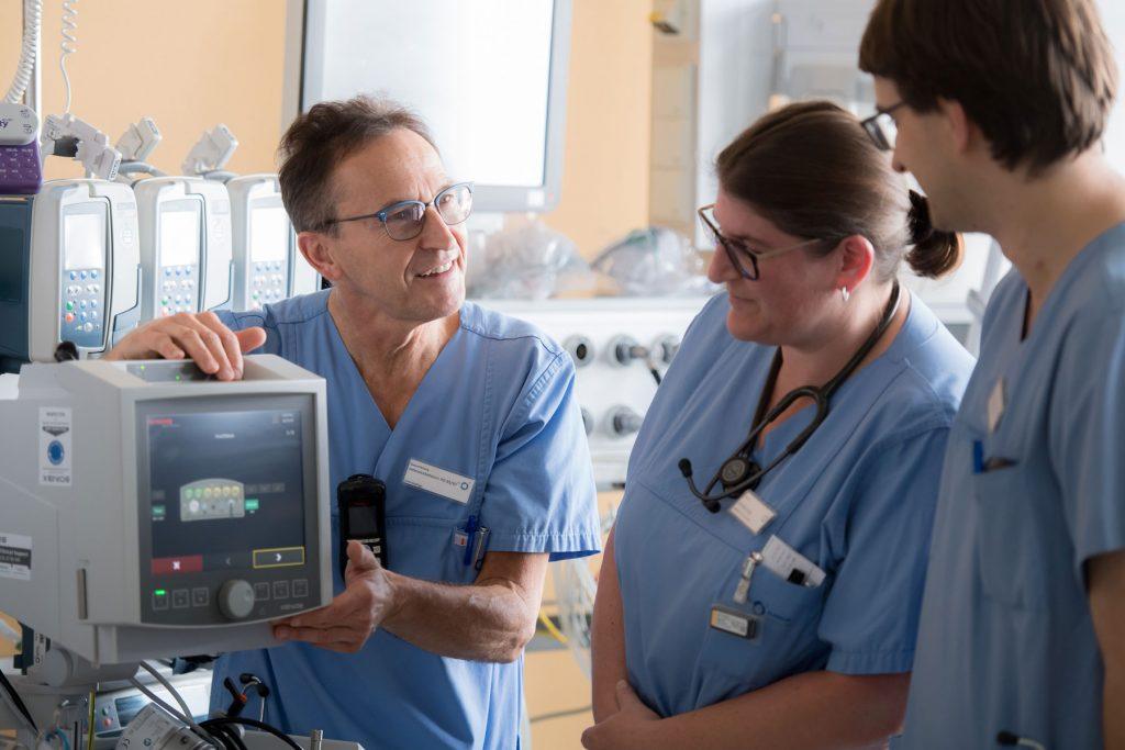 Der leitende Intensivpfleger erklärt zwei Kollegen die Bedienung eines Überwachungsgerätes auf der Intensivstation des Klinikums Ingolstadt