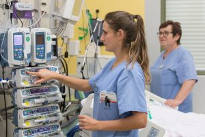 Eine Pflegefachkraft kontrolliert auf der Intensivstation die Vitalwerte eines Patienten.