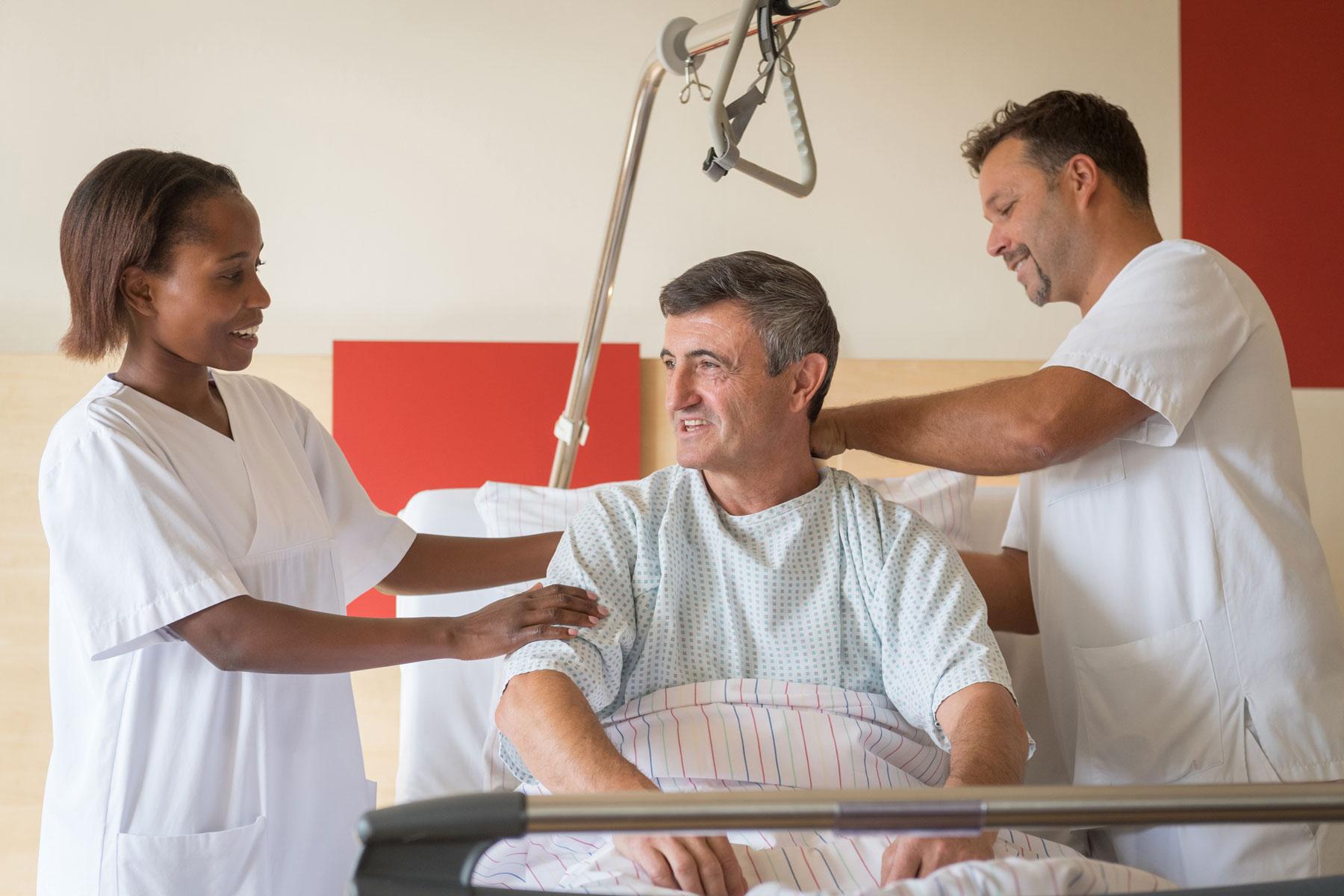 Zwei Pflegekräfte in der Ausbildung helfen einem Herren beim Aufstehen aus dem Krankenbett