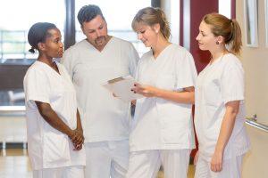 Vier Pflegekräfte sehen sich die Dokumentation zu einem Patienten an.