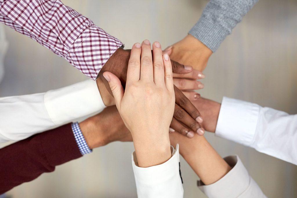 Ein Bild von verschiedenen Personen, die ihre Hände übereinander legen