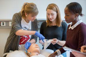 Drei Auszubildende des Klinikums Ingolstadt üben an einer Puppe das Legen eines Venenzugangs