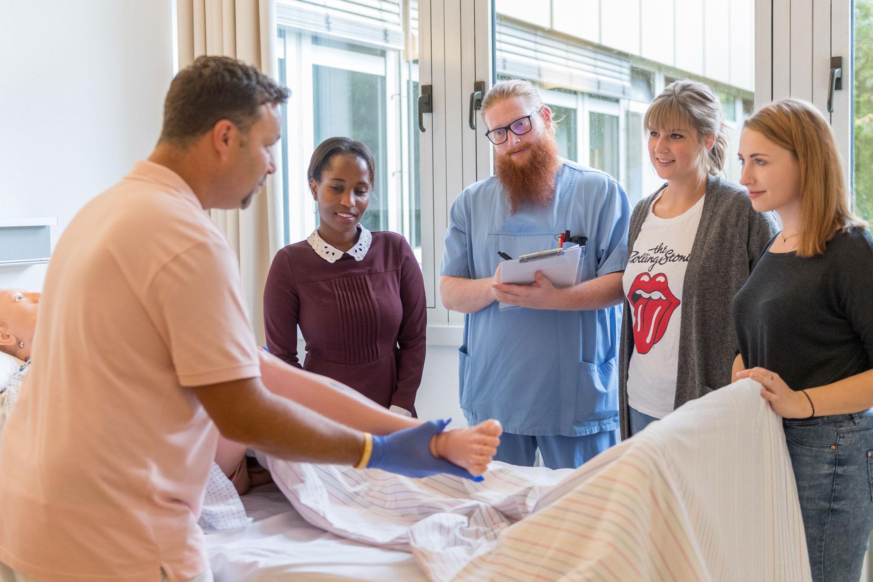 Eine Pflegefachkraft zeigt an einer Puppe wie man einen Patienten im Bett richtig umlagert.