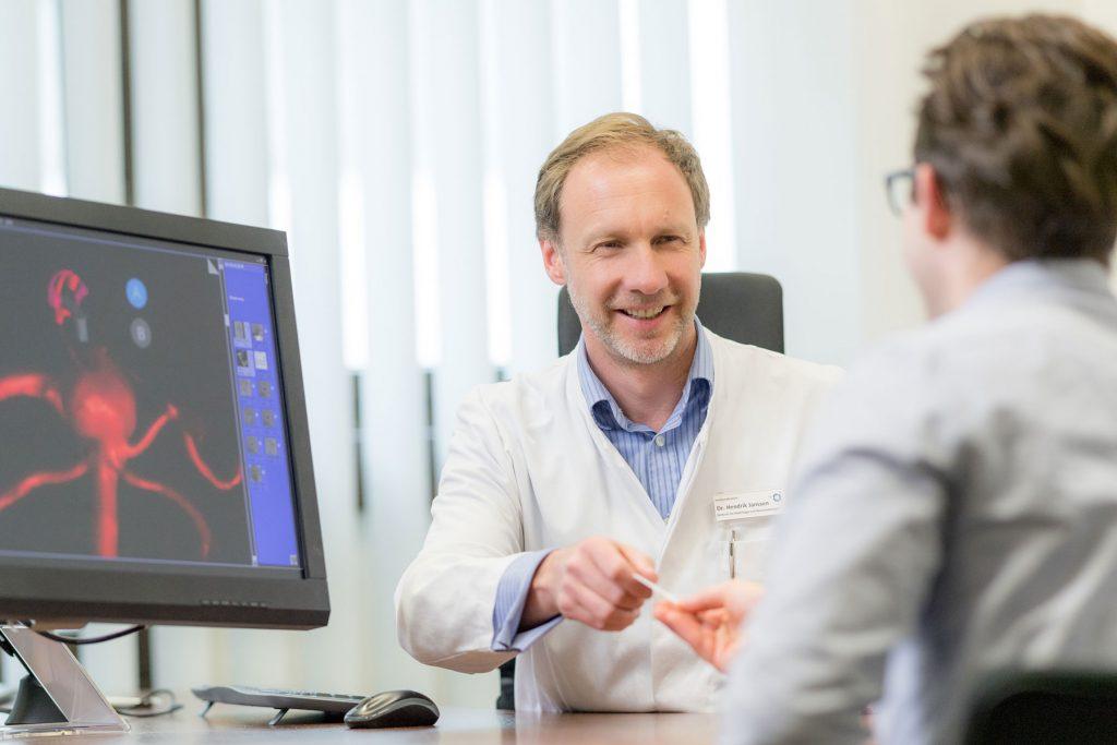 Dr. Hendrik Janssen übergibt einem Patienten im Gespräch seine Visitenkarte